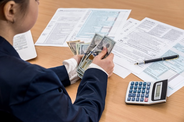 La signora di affari lavora con dollari e 1040 documenti fiscali