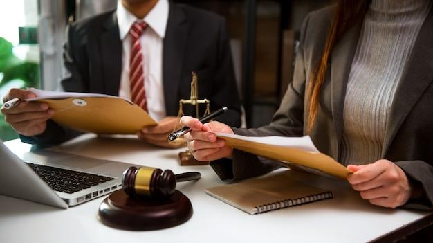 Affari e avvocati discutono di documenti contrattuali con bilancia in ottone sulla scrivania in ufficio. legge, servizi legali, consulenza, giustizia e concetto di diritto.
