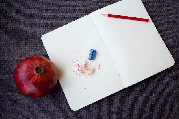 Concetto di affari, stile di vita, cibo e caffè - taccuino con matita e trucioli di matita su uno sfondo di panno marrone