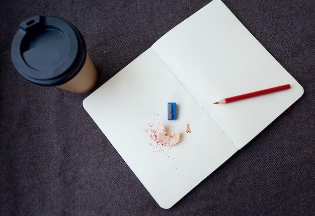 Concetto di affari, stile di vita, cibo e caffè: matita, taccuino e tazza da caffè di carta su uno sfondo di tessuto marrone