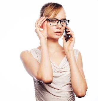 Concetto di affari, stile di vita e persone: giovane donna d'affari con gli occhiali con il telefono cellulare.
