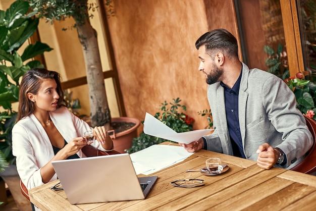 Pranzo di lavoro uomo e donna seduti a tavola al ristorante che discutono del progetto vivace