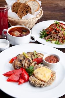 Pranzo di lavoro cotoletta con funghi fritti e peperoni dolci con insalata mista