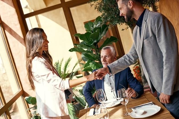 Pranzo di lavoro tre persone al ristorante a tavola giovane donna che stringe la mano a un uomo