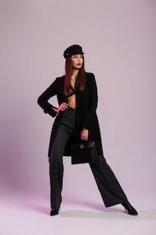 Giovane donna lussuosa di affari con labbra sexy rosse in reggiseno di pizzo in elegante berretto in giacca lunga in pantaloni a righe in stivali eleganti con borsa di moda in pelle in posa in studio. modello di ragazza attraente.