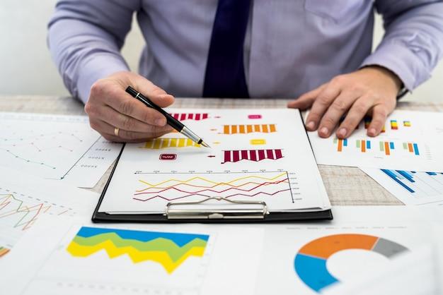Un uomo d'affari analizza le entrate e i grafici in ufficio. analisi aziendale e concetto di strategia. l'uomo d'affari sviluppa un progetto commerciale e analizza le informazioni di mercato, sessione fotografica dall'alto