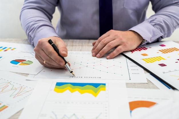 Un uomo d'affari analizza le entrate e grafici in ufficio. analisi aziendale e concetto di strategia.