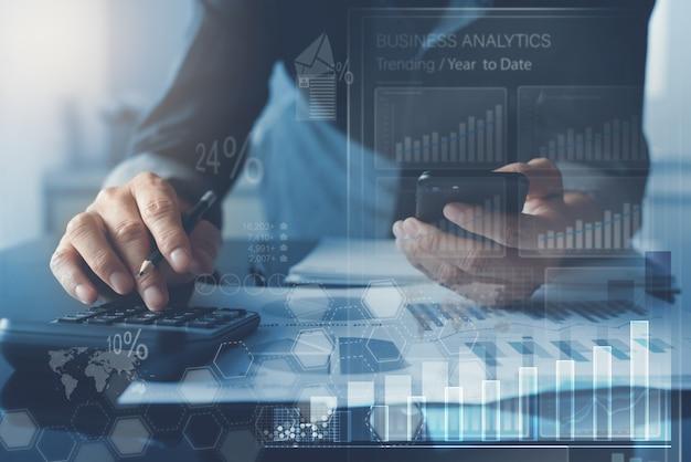 Uomo di affari che analizza il rapporto di mercato con il cruscotto di analisi dei dati di affari sullo schermo virtuale