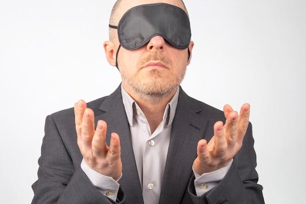 Uomo d'affari in una benda per dormire con le mani in alto