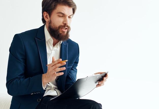 Uomo d'affari in una giacca blu e in una camicia bianca con documenti in una cartella su uno sfondo chiaro