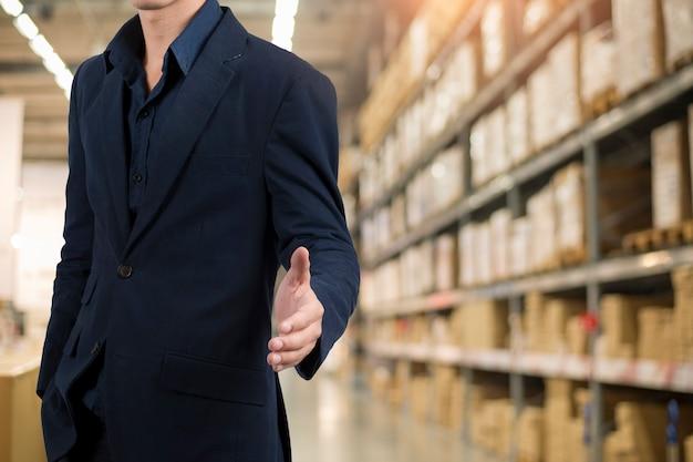 Uomo di affari in vestito blu che si leva in piedi sopra la priorità bassa del magazzino