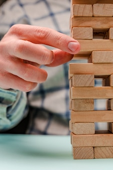 L'uomo d'affari costruisce una torre di blocchi di legno come simbolo di sviluppo e pianificazione nel mondo degli affari