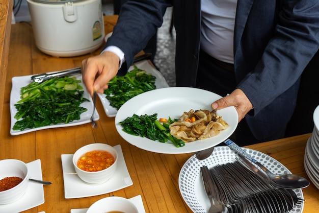 Uomo di affari in vestito di affari che prepara la tagliatella fritta con carne di maiale e broccoli per il pranzo.