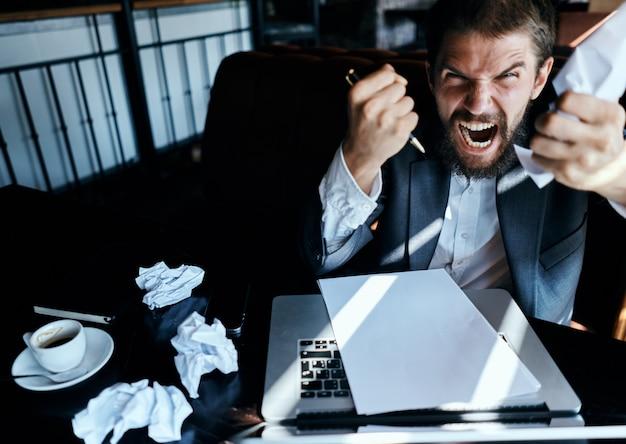 Uomo d'affari in un caffè seduto al tavolo documenti laptop carta stropicciata emozioni esecutive stile di vita