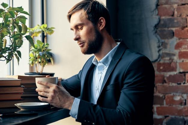 Uomo d'affari in un caffè vestito bere caffè resto colazione