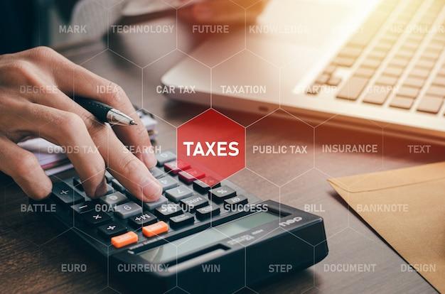 Uomo d'affari che calcola le tasse passate con icone che mostrano come una tabella sullo schermo deducibili dalle tasse è il concetto di tasse pagate da individui e nuclei.