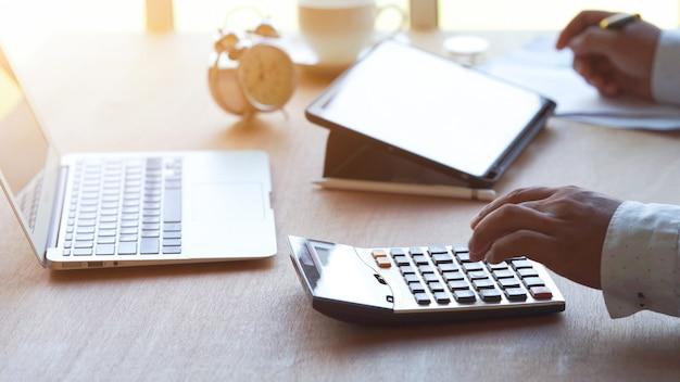 Uomo d'affari che calcola la gestione delle tasse e del denaro