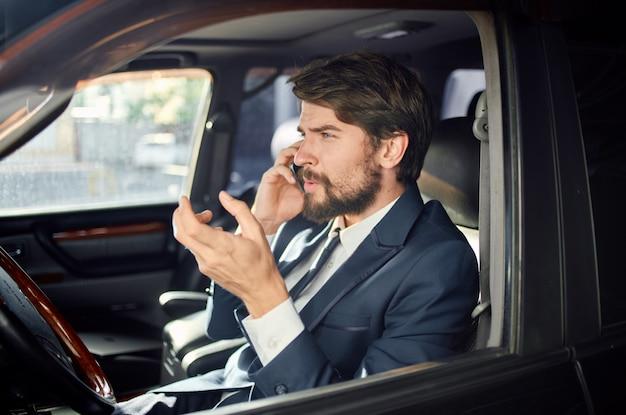 Uomo d'affari in un salone di automobile parlando al telefono in un vestito