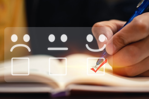 Uomo d'affari segno di spunta faccia sorriso emoticon sulla casella della lista di controllo per rivedere una buona valutazione
