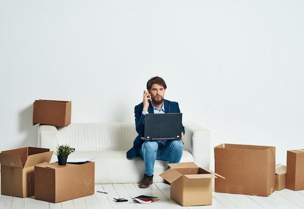 Uomo d'affari sul divano con scatole che trasportano cose nuovo luogo di lavoro