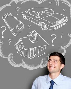 Uomo d'affari sognando l'acquisto di casa, auto o gadget