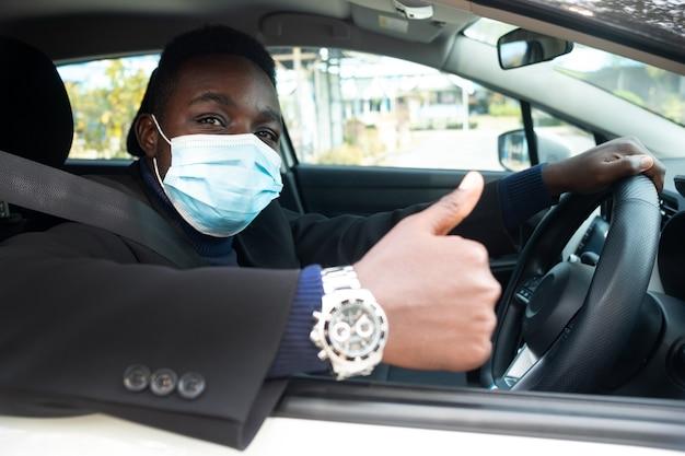 Uomo d'affari alla guida di auto con indossando maschera medica