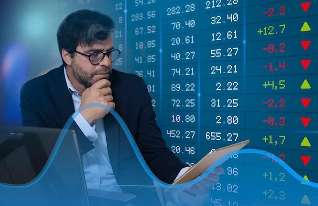 Uomo d'affari che segue l'evoluzione dei grafici del mercato azionario sul tablet - messa a fuoco selettiva