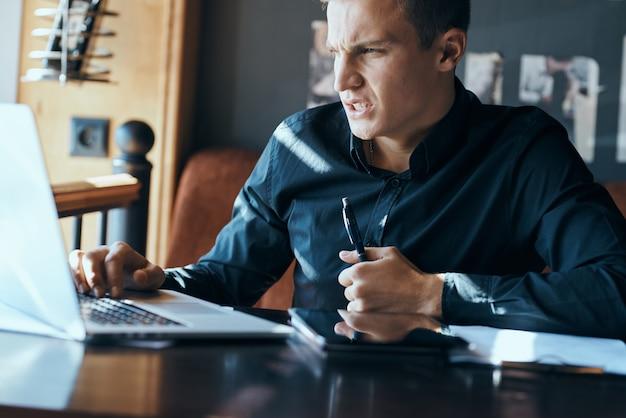 Libero professionista dell'uomo di affari con il computer portatile in caffè al modello della tazza del caffè dei documenti del gestore della tabella.