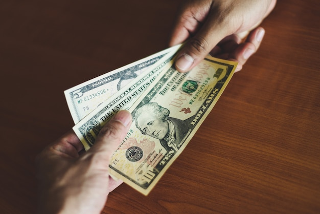 L'uomo di affari dà il concetto del dono dei soldi - la persona passa l'uomo che dà i soldi sui contanti di paga del fondo della tavola di legno sulla paga di consegna per ricevere i soldi