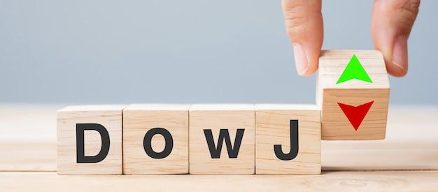 Blocco cubo di legno del cambiamento della mano dell'uomo di affari con il testo di dow j sull'icona del simbolo della freccia su e tasso di interesse, azioni, finanziaria, classifica, tassi ipotecari e concetto di perdita di taglio