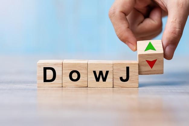 Blocco di legno del cubo del cambio della mano dell'uomo di affari con il testo di dow j al simbolo su e giù della freccia