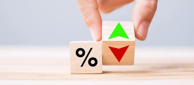 Blocco cubo di legno del cambiamento della mano dell'uomo di affari con la percentuale sull'icona del simbolo della freccia su e giù. tasso di interesse, azioni, finanziaria, classifica, tassi ipotecari e concetto di perdita di taglio