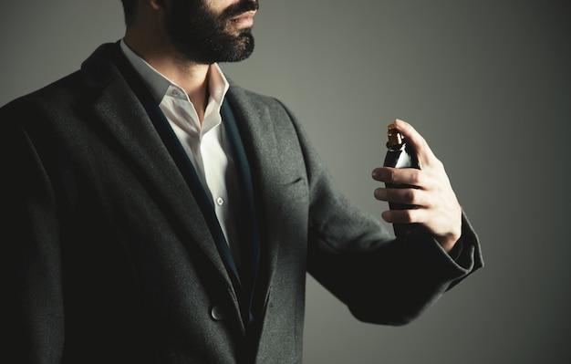 Mano dell'uomo di affari che tiene la bottiglia di profumo