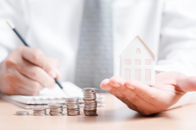 Modello della casa della tenuta della mano dell'uomo di affari con la fila della moneta e la fabbricazione delle note