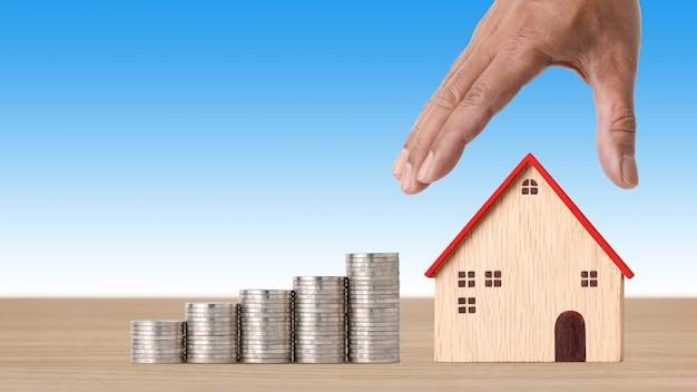 Mano dell'uomo d'affari che tiene la casa modello e impila le monete sulla scrivania di legno su sfondo blu