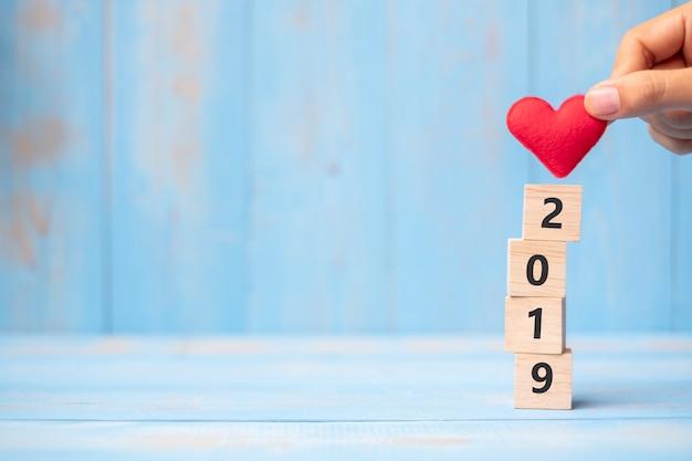 La mano dell'uomo di affari che tiene il cuore rosso modella oltre 2019 cubi di legno sul fondo blu della tavola con lo spazio della copia per testo. affari, risoluzione, anno nuovo, nuovo e buon giorno di san valentino