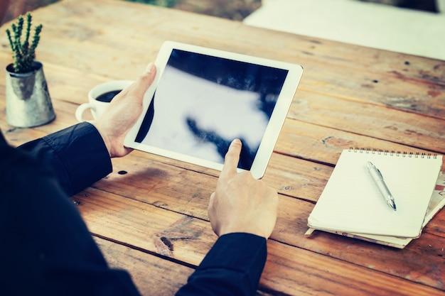 Uomo di affari azienda mano e utilizzando tablet su tavola in caffè con filtro tonica vintage.