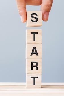 Mano dell'uomo d'affari che tiene il blocco di legno con testo start sullo sfondo della tabella. obiettivi, mentalità, strategia, nuovi concetti di avvio e di business