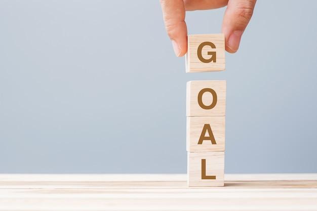 Mano dell'uomo di affari che tiene il blocco cubo di legno con la parola di affari di obiettivo obiettivo, obiettivo, missione, azione e concetto di piano