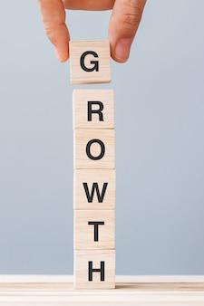 Mano dell'uomo di affari che tiene il blocco cubo di legno con la parola di affari di crescita. concetto di successo, profitto, economia e finanza