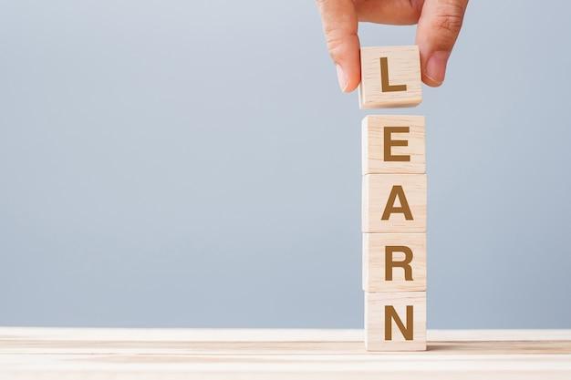 Mano dell'uomo di affari che tiene il blocco cubo di legno con impara parola di affari sullo sfondo della tabella. apprendimento, educazione conoscenza, studio e saggezza