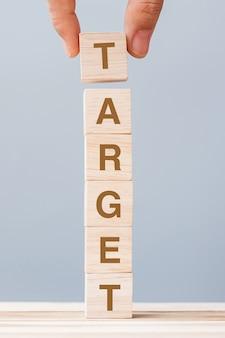 Mano dell'uomo d'affari che tiene il blocco cubo di legno con la parola d'affari target. obiettivo, scopo, missione, azione e concetto di piano