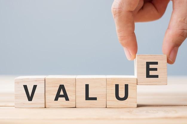 Mano dell'uomo di affari che tiene il blocco cubo di legno con la parola di affari di valore sul fondo della tavola. concetto di missione, visione e valori fondamentali