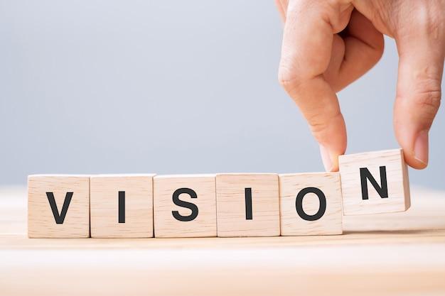 Mano dell'uomo d'affari che tiene il blocco cubo di legno con la parola d'affari vision sullo sfondo della tavola. strategia, missione e concetto di valori fondamentali