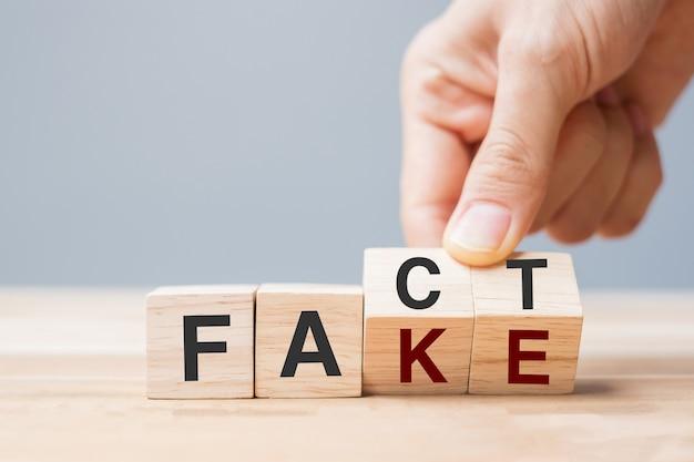 Mano dell'uomo d'affari che tiene cubo di legno con blocco ribaltabile falso a fatto. rumor notizie, falsi, miti, prove e concetti di disinformazione