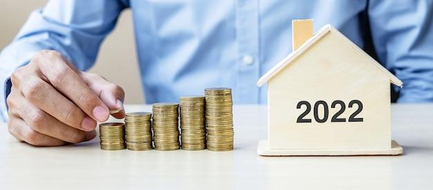 Mano dell'uomo d'affari che mette moneta d'oro sulle scale di denaro in crescita con casa in legno 2022. felice anno nuovo affari, investimenti, pianificazione della pensione, finanza, risparmio e nuovi concetti di te
