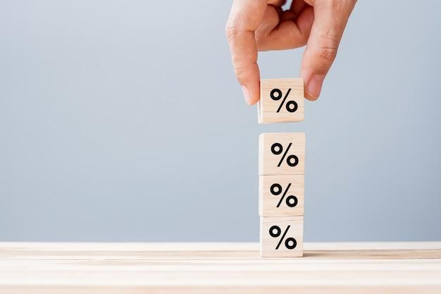 Mano dell'uomo di affari che mette blocco cubo di legno con l'icona del simbolo di percentuale. tasso di interesse, concetto finanziario, di classifica e di tassi ipotecari