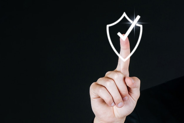Uomo d'affari mano toccando scudo segno di spunta icona schermo virtuale diagramma grafico su sfondo scuro, sicurezza internet, innovazione, connessione di rete, investimento e concetto di tecnologia digitale
