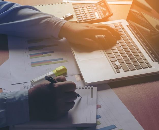 Mano d'affari di lavoro sul computer intelligente e computer portatile e diagramma di business diagram grafico su tavola di legno con riflessione finestra in ufficio.