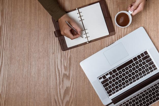 Mani dell'uomo d'affari utilizzando un computer portatile con una tazza di caffè e uno smartphone con spazio per le copie.